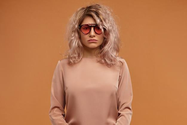Expressions faciales humaines et émotions. insatisfait bouleversé jeune femme portant des lunettes de soleil élégantes étant de mauvaise humeur, ayant l'air ennuyé