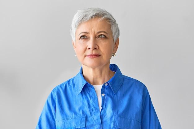 Expressions faciales humaines. image de la créatrice européenne élégante à la mode réfléchie avec coupe de cheveux de lutin en levant avec un sourire songeur de rêve, inspirée par une idée créative soudaine