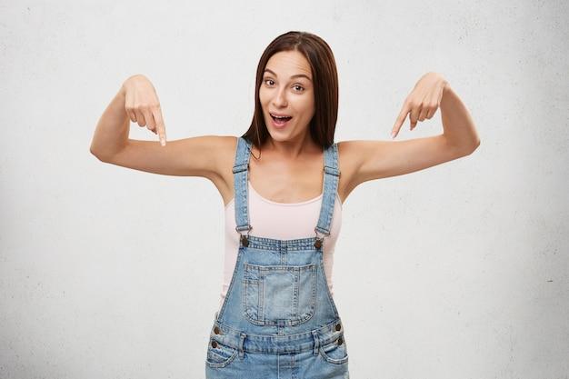 Expressions faciales humaines positives. excitée ou étonnée jeune femme d'apparence européenne posant, pointant du doigt vers le bas, s'exclamant de choc et d'étonnement
