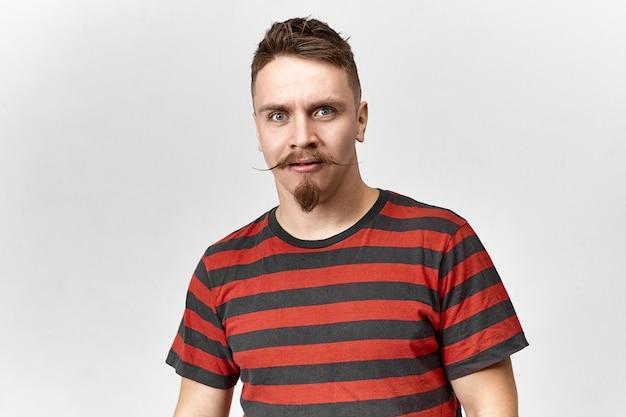 Expressions faciales humaines et réaction. vue isolée de drôle de jeune homme élégant avec une moustache cirée et une barbe taillée regardant la caméra en pleine incrédulité, ayant regard surpris méfiant