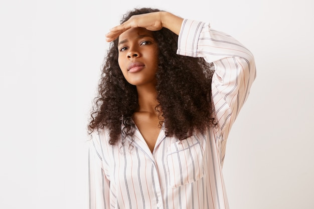 Expressions faciales humaines, réactions et émotions. jolie jeune femme africaine en pyjama élégant tenant la paume sur son front, regardant au loin, essayant de voir clairement, ayant un regard concentré