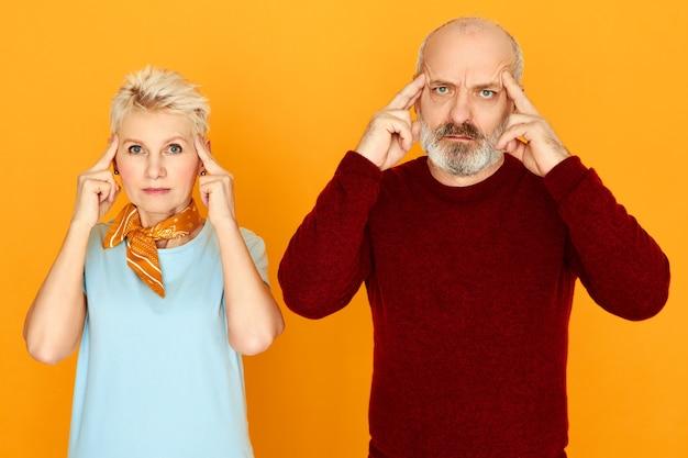 Expressions faciales humaines, réactions et sentiments. pensive couple retraité femme aux cheveux gris et mari chauve tenant les doigts sur les tempes ayant concentré les regards, souffrant de maux de tête