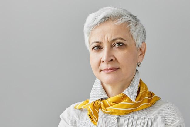 Expressions faciales humaines, sentiments, émotions et réactions. close up belle retraité femme d'âge moyen avec de courts cheveux gris fronçant les sourcils, ayant concentré regard sérieux