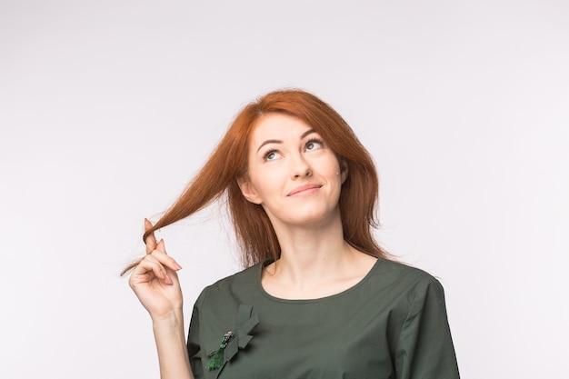 Expressions et personnes concept portrait d'une belle jeune femme aux cheveux rouges pensant sur blanc