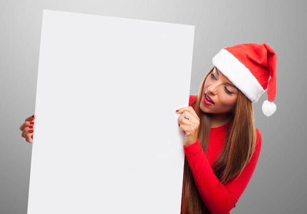 Expressive jeune femme tenant une pancarte en blanc