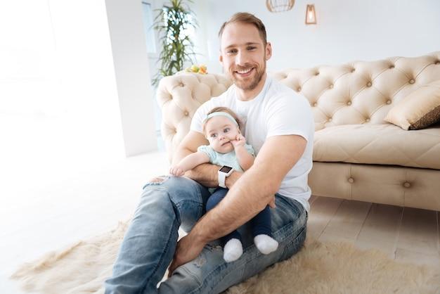 Exprimer la positivité ensemble. petite fille positive concentrée assise avec son père à la maison et regardant ailleurs tout en exprimant son intérêt et son bonheur