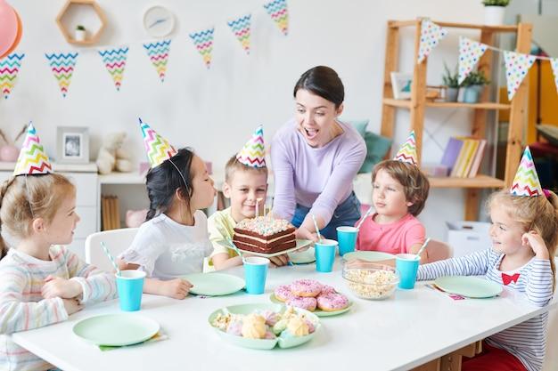 Extatique jeune femme tenant un gâteau d'anniversaire et à la recherche de bougies tandis que l'une des petites filles les souffle par table servie entre amis