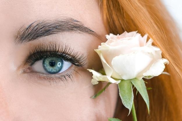 Extension de cils. macro bel oeil avec de longs cils avec une rose