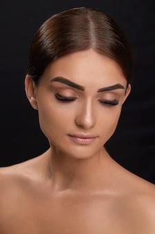 Extensions de cils. faux cils. gros plan de la belle jeune mannequin avec une peau douce et lisse et un maquillage facial professionnel. portrait d'une fille sexy avec de longs cils faux et un maquillage parfait.