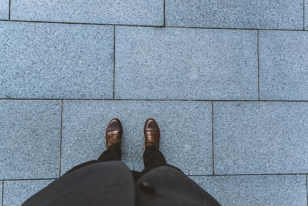 À l'extérieur, dans la ville, gros plan sur les jambes d'un homme, pantalon et chaussures classiques.