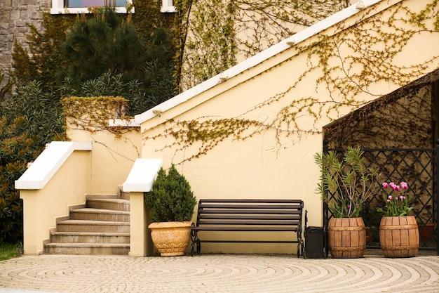 Extérieur de la maison décoré de pots de fleurs faits de vieux tonneaux en bois.
