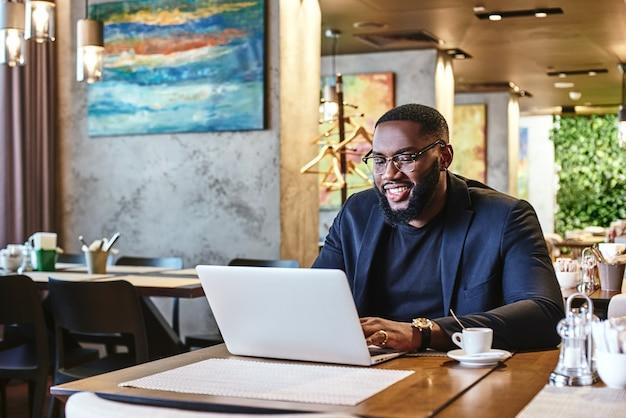 À l'extérieur pour déjeuner, un homme d'affaires afro-américain travaille à l'aide de son ordinateur portable tout en se reposant dans le