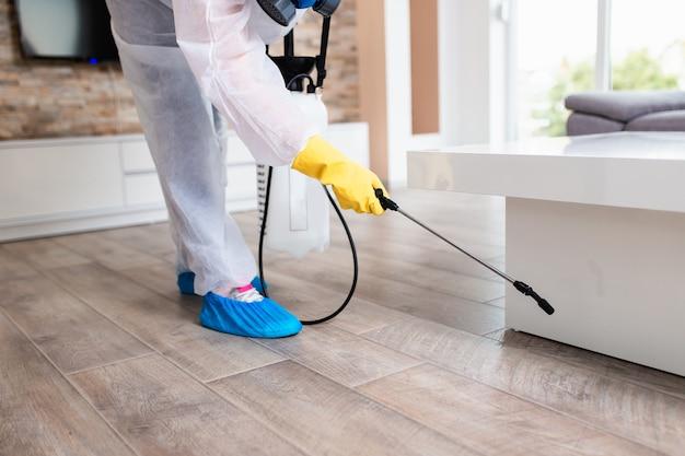Exterminateur en vêtements de travail pulvérisant des pesticides avec un pulvérisateur.