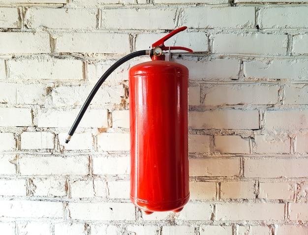 Extincteur à poudre pour éteindre un incendie en gros plan sur un fond isolé en brique blanche