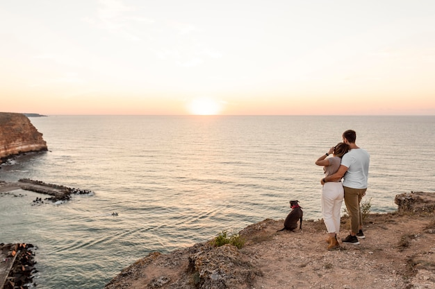 Extra long shot couple regardant le coucher du soleil avec leur chien