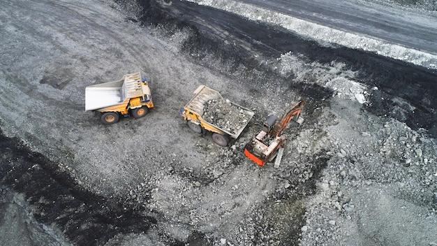 Extraction de charbon dans une carrière. une pelle hydraulique charge un camion à benne basculante.