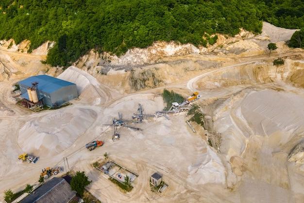 Extraction à ciel ouvert de matériaux de pierre de sable de construction avec des excavatrices et des camions à benne basculante à la bande transporteuse.
