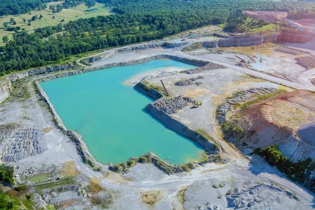 Extraction de pierres à ciel ouvert dans le canyon avec un lac vert profond
