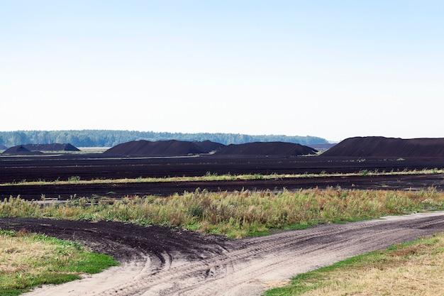 Extraction de tourbe - une zone dans laquelle la production est réalisée de la tourbe noire, des montagnes de tourbe