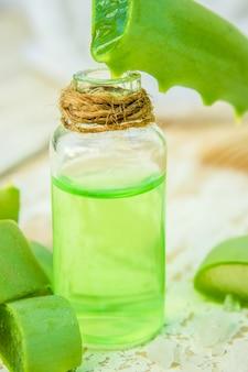 Extrait d'aloe vera dans une petite bouteille et des morceaux sur la table. mise au point sélective.