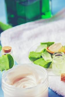 Extrait d'aloe vera dans une petite bouteille et morceaux sur la table. mise au point sélective.