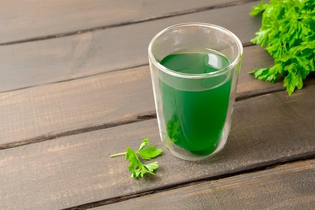 Extrait de chlorophylle de boisson de désintoxication saine avec de l'eau dans une tasse en verre sur une table en bois avec espace de copie