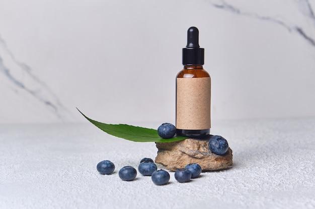 Extrait cosmétique de myrtille de soins de la peau pour spa, vitamines pour la santé, effet frais, tube blanc avec crème écologique naturelle pour la peau du visage. cosmétique bio. ingrédients de myrtille, bouteille brune sur le support en pierre