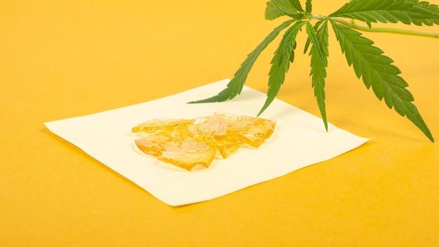 Extrait fort de cire de cannabis dorée à haute teneur en thc sur fond jaune en gros plan.