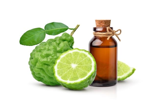 Extrait d'huile essentielle de bergamote en bouteille ambrée avec fruit de bergamote isolé sur blanc.