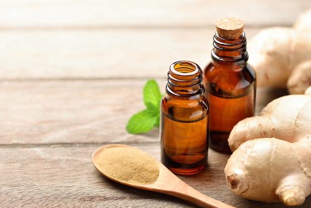 Extrait d'huile essentielle de gingembre avec poudre et rhizome sur table en bois.