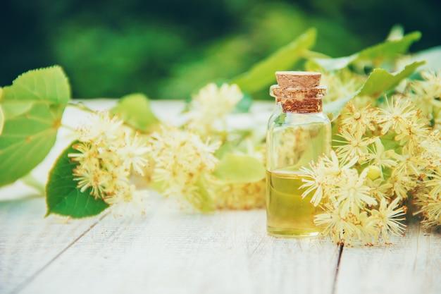 Extrait de tilleul et fleurs dans une petite bouteille. mise au point sélective.
