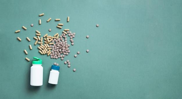 Extraits d'eucalyptus en gélules, pilules, comprimés sur fond vert avec espace copie.