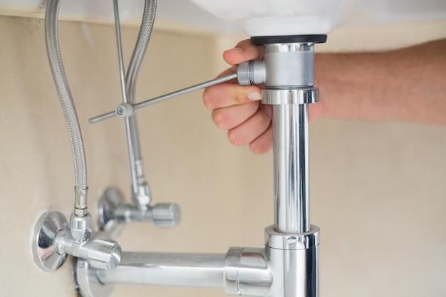 Extreme gros plan d'une main de plombier et drain de lavabo