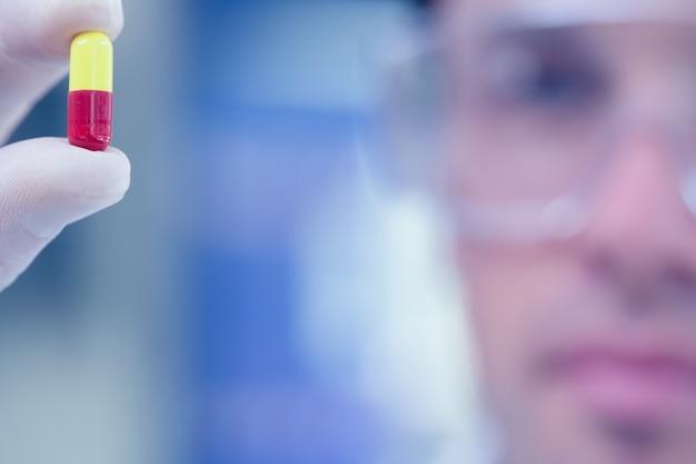 Extrême gros plan d'un scientifique analysant une pilule