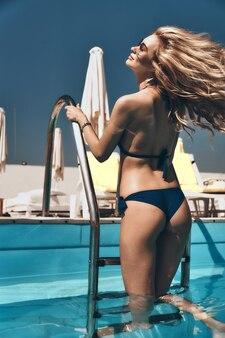 Extrêmement sensuel. jolie jeune femme en maillot de bain gardant les yeux fermés et souriant tout en sortant de la piscine