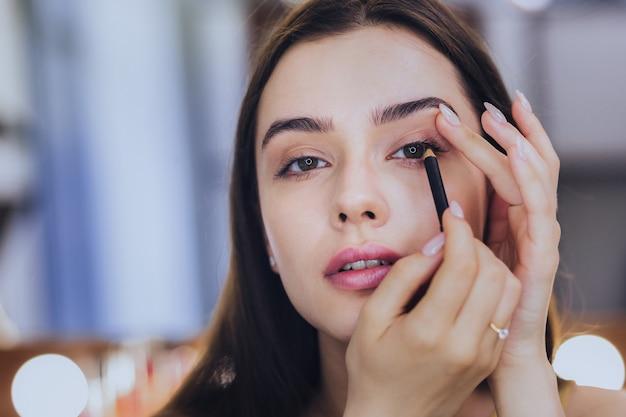 Eye-liner noir. incroyablement belle jeune femme aux cheveux noirs utilisant un eye-liner noir tout en se maquillant