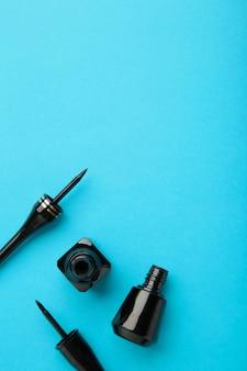 Eyeliners sur fond bleu avec espace de copie. vue de dessus. photo verticale