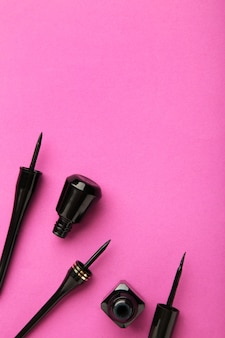 Eyeliners sur fond rose avec espace de copie. vue de dessus. photo verticale
