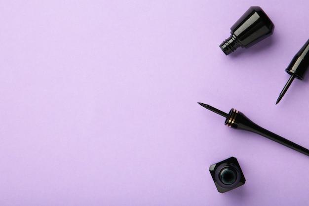 Eyeliners sur fond violet avec espace de copie. vue de dessus. notion de beauté