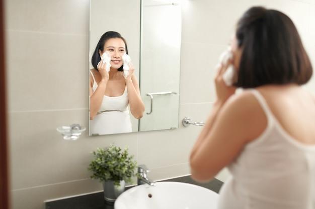 F belle femme enceinte lave son visage dans la salle de bain