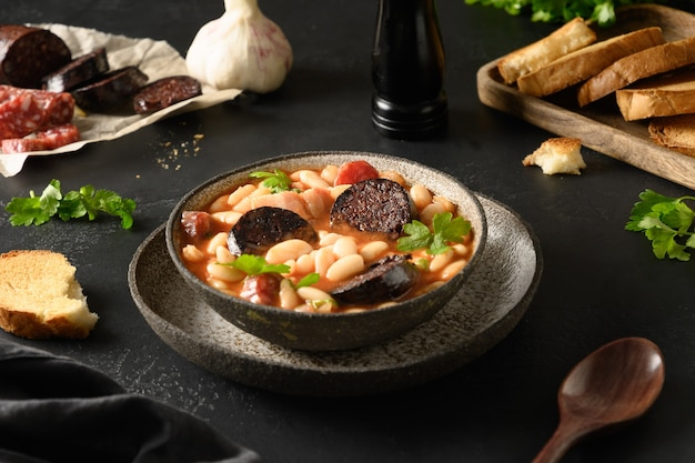 Fabada asturiana espagnole avec chorizo et morcilla sur fond noir