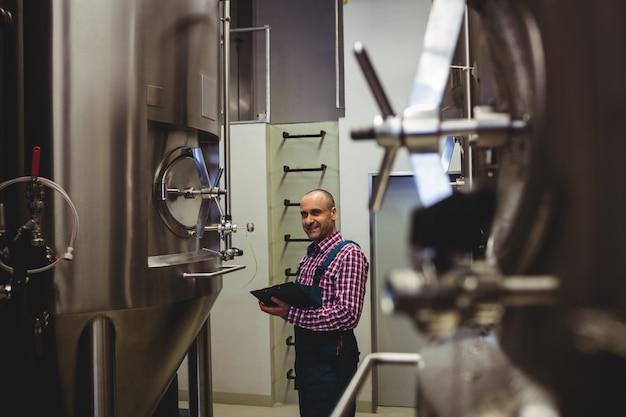 Le fabricant écrit dans le presse-papiers lors de l'examen des machines