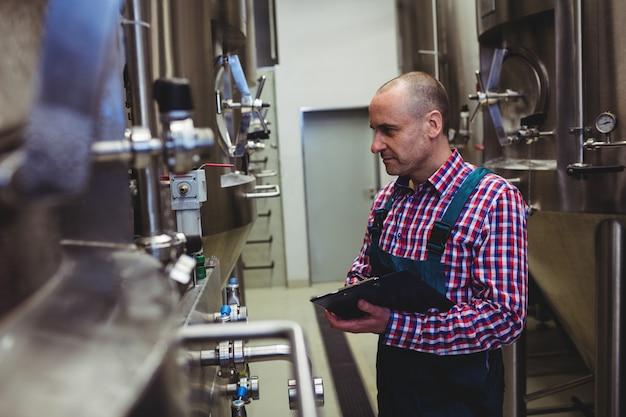 Fabricant examinant des machines à la brasserie