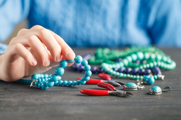 Fabrication de bijoux faits main. boîte avec perles et coeurs en verre sur une vieille surface en bois. accessoires artisanaux