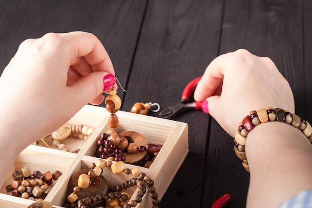 Fabrication de bijoux faits main. boîte avec perles sur une vieille table en bois.