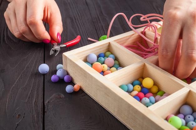 Fabrication de bijoux et processus de perlage. perles colorées. bijoux en perles