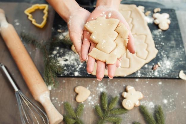 Fabrication de boulangerie maison, biscuits en pain d'épice sous forme de gros plan d'arbre de noël. gâterie du nouvel an pour la cuisine du père noël