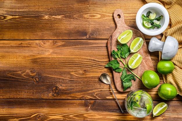 Fabrication de cocktails mojito. ingrédients menthe, citron vert, glace et ustensiles de bar.