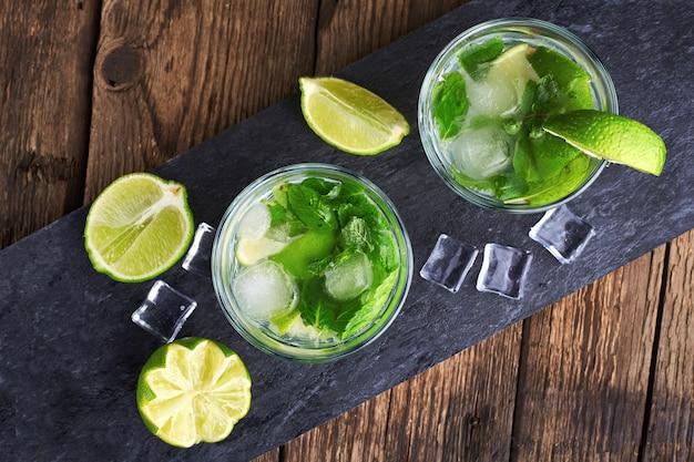Fabrication de cocktails mojito. menthe, citron vert, ingrédients glacés et ustensiles de bar. vue de dessus