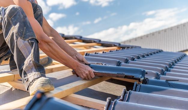 Fabrication du toit d'une maison familiale à partir de tuiles céramiques. copie espace